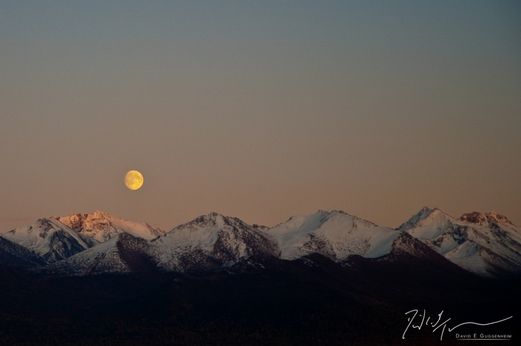 """""""Alaska Moon"""" - A full moon rises above the snow-covered mountains of Anchorage, Alaska."""